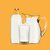 Pouring milk in transparent glass with splash, lot of drops and full jug of milk standing behind Stock Images