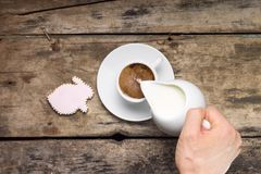Pouring milk in White Cup of Coffee. Coffee with gingerbread rabbit on wood background. Stock Image