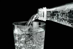 Pouring mineral water in the glass. Close up image on black background Stock Photos