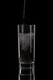 Pouring mineral water in simple highball glass Royalty Free Stock Image