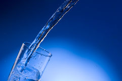 Pouring mineral water stream into a glass Royalty Free Stock Photos