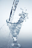 Pouring mineral water stream into a glass Royalty Free Stock Images