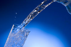 Pouring mineral water stream into a glass Stock Photography