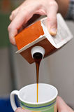 Pouring molasses. In a mug from a carton Royalty Free Stock Photos