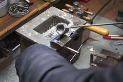 Pouring molten lead alloy into a mold. Workshop. Royalty Free Stock Photo