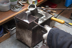 Pouring molten lead alloy into a mold. Workshop. Stock Photography