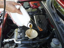 Pouring Motor Oil. Male adding oil with a funnel after a do-it-yourself oil change. Dipstick is nearby Stock Photography