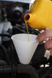 Pouring motor oil in the engine. Closeup of a man pouring motor oil into a funnel into a car engine Stock Image