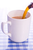 Pouring mug of tea. Tea poured into a large cup reflected on blue ginham surface royalty free stock photos