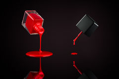 Pouring Nail Polish. Red nail polish pouring out from the bottle and dripping from cap brush, on a reflective surface stock images