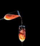 Pouring Neon Liquid. Glass of orange neon liquid pouring into another Stock Photo