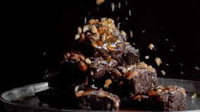 Pouring nuts onto brownie in slow motion. Arm takes peace of brownie stock footage