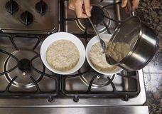 Pouring Oatmeal into Breakfast Bowls Stock Photos