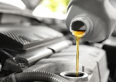 Pouring oil into car engine stock photography