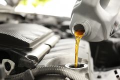 Pouring oil into car engine. Closeup royalty free stock photos