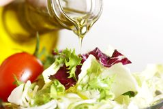Pouring oil. Close-up of bottle with pouring olive oil and vegetable salad stock images