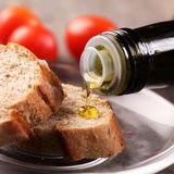Pouring oil. Close-up of olive oil pouring on slices of bread stock images