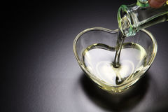 Pouring oil. Pouring grape seed oil into heart shape container stock image