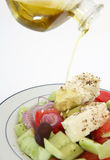 Pouring oil on Greek salad vertical Stock Image