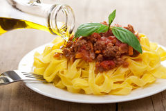 Pouring oil over tagliatelle bolognese Royalty Free Stock Photos