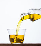 Pouring olive oil from a bottle into a glass Stock Photos