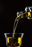 Pouring olive oil from a bottle into a glass Royalty Free Stock Image