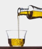 Pouring olive oil from a bottle into a glass Royalty Free Stock Photos