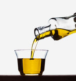 Pouring olive oil from a bottle into a glass Royalty Free Stock Images