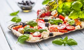 Pouring olive oil on caprese salad. Healthy italian or mediterranean meal royalty free stock photo