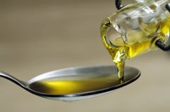 Pouring olive oil. Extra virgin olive oil pouring from bottle to spoon closeup royalty free stock image