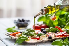 Pouring Olive Oil On Caprese Salad. Healthy Italian Or Mediterranean Meal Stock Photography