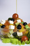 Pouring olive oil onto Greek salad Royalty Free Stock Image
