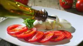 Pouring olive oil over caprese salad stock video footage