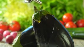 Pouring olive oil over an eggplant stock video footage