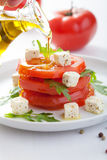 Pouring olive oil over salad with beef tomatoes and feta Royalty Free Stock Images