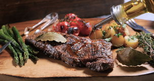 Pouring olive oil over a sirloin steak with asparagus, potatoes and roasted tomatoes stock footage