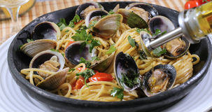 Pouring olive oil over spaghetti alle vongole clams Royalty Free Stock Photo