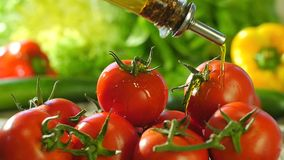 Pouring olive oil over tomatoes. Fresh tomatoes and olive oil bottle close up slow motion