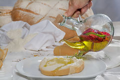 Pouring olive oil on a slice of bread. On a plate Stock Photo