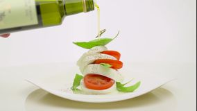 Pouring olive oil with  tomatos and mozzarella stock video