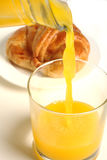 Pouring orange juice croissant behind Stock Images