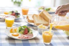Pouring Orange Juice For Breakfast Stock Photo