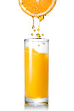 Pouring orange juice from orange into the glass Stock Images