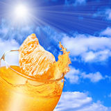 Pouring orange juice from orange into the glass Royalty Free Stock Images