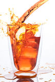 Pouring orange water in to clear glass Stock Image