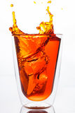 Pouring orange water in to clear glass Royalty Free Stock Image