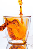 Pouring orange water in to clear glass Stock Photography