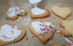 Glazing cookies. Pouring over glazing mass over dough pieces Royalty Free Stock Photo