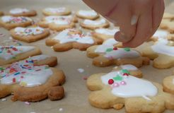 Glazing cookies. Pouring over glazing mass over dough pieces Royalty Free Stock Photos