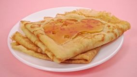 Pouring pancakes with syrup on pink background stock video footage